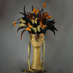 Beautiful Masquerade Mask, in shades of black and Metallic copper.Crested with black coque feathers and assorted dyed plumage. Orange and gold feather Monarch butterflies flutter on the crest. Embellished with Swarovski crystals, seashells and polished stones.  Hand made in the USA using traditional Venetian paper-mache technique. Lined with hypoallergenic stretch velvet for comfort.