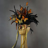Beautiful Masquerade Mask, in shades of black and Metallic copper.Crested with black coque feathers and assorted dyed plumage. Orange and gold feather Monarch butterflies flutter on the crest. Embellished with Swarovski crystals, seashells and polished stones.  Hand made in the USA using traditional Venetian paper-mache technique. Lined with hypoallergenic stretch velvet for comfort. Side view.