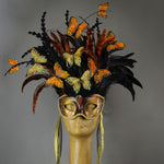 Beautiful Masquerade Mask, in shades of black and Metallic copper.Crested with black coque feathers and assorted dyed plumage. Orange and gold feather Monarch butterflies flutter on the crest. Embellished with Swarovski crystals, seashells and polished stones.  Hand made in the USA using traditional Venetian paper-mache technique. Lined with hypoallergenic stretch velvet for comfort. Detail.