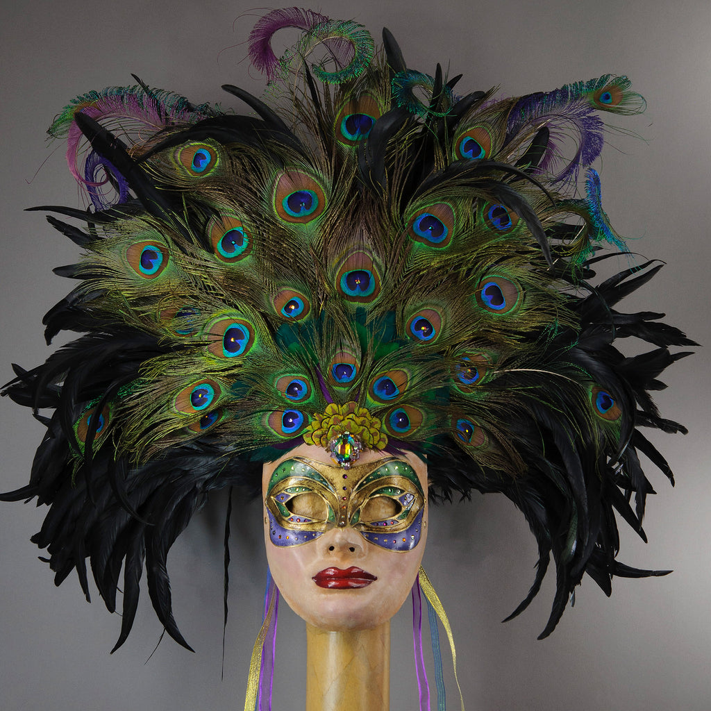 Stunning Full Face Mask with a luxe crest of black coque and assorted peacock tail feathers and plumage. Embellished with Swarovski crystals, and assorted polished gem stones. Sure to turn heads at any costume, masquerade or Halloween party!  Hand-made in the USA using traditional Venetian paper-mache technique. Lined with hypoallergenic stretch velvet for comfort.