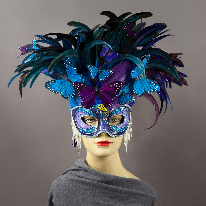 Beautiful Masquerade Mask, in shades of purple and blue. Crested with black, purple and blue hand dyed coque feathers and assorted plumage. Purple and blue feather Monarch butterflies flutter on the crest. Embellished with Swarovski crystals, seashells, freshwater pearls and polished stones with a small tree frog perched on top.  Hand made in the USA using traditional Venetian paper-mache technique. Lined with hypoallergenic stretch velvet for comfort.