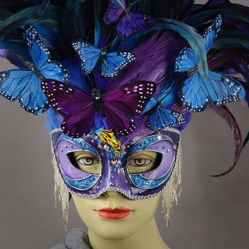 Beautiful Masquerade Mask, in shades of purple and blue. Crested with black, purple and blue hand dyed coque feathers and assorted plumage. Purple and blue feather Monarch butterflies flutter on the crest. Embellished with Swarovski crystals, seashells, freshwater pearls and polished stones with a small tree frog perched on top.  Hand made in the USA using traditional Venetian paper-mache technique. Lined with hypoallergenic stretch velvet for comfort. Detail.