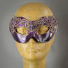 Metallic purple and black mask with butterfly motif lace accented in gold. Embellished with Swarovski crystals and polished gems.