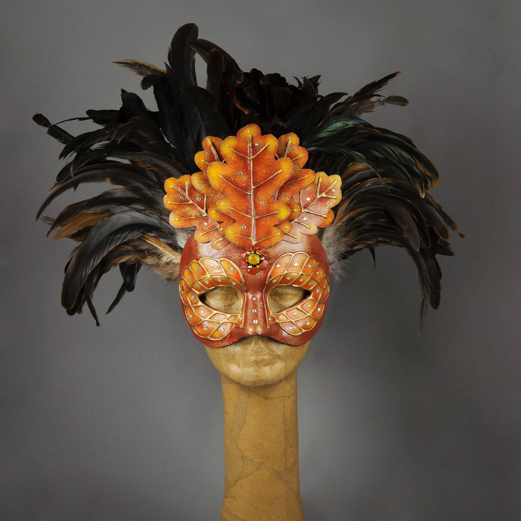 Beautiful Masquerade Mask, crested in Black coque feathers accented with red and gold handmade oak leaves. Embellished with Swarovski crystals, dichroic glass and polished stones. This is one of our versions of the Green Man mask in shades of red and gold to reflect the autumn/fall.  Hand made in the USA using traditional Venetian paper-mache technique. Lined with hypoallergenic stretch velvet for comfort.