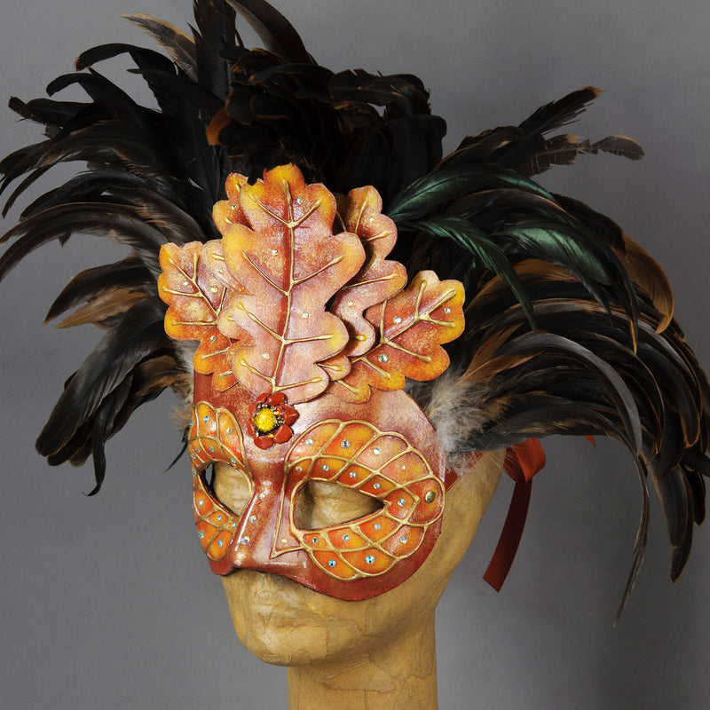 Beautiful Masquerade Mask, crested in Black coque feathers accented with red and gold handmade oak leaves. Embellished with Swarovski crystals, dichroic glass and polished stones. This is one of our versions of the Green Man mask in shades of red and gold to reflect the autumn/fall.  Hand made in the USA using traditional Venetian paper-mache technique. Lined with hypoallergenic stretch velvet for comfort. Side view.