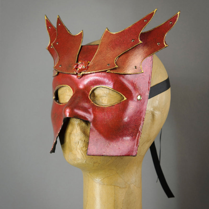 Bronze Warrior Bauta Masquerade mask, with panel armor, metal findings and assorted polished gems. Inspired by medieval armor, this mask is particularly popular for men.  Handmade in the USA using traditional Venetian paper-mache technique. Lined with hypoallergenic stretch velvet for comfort. Side view.