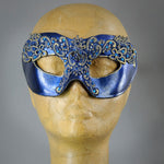 Simple, elegant eye mask in Metallic Sapphire Blue and Black with gold accents. Embellished with lacquered lace, glass gems, Swarovski crystals and polished stones.  Hand made in the USA using traditional Venetian paper-mache techniques. Lined in stretch velvet for comfort.