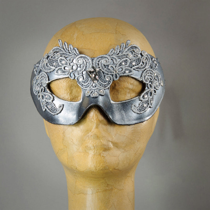 Simple, elegant eye mask in Metallic Silver and Black. Embellished with lacquered lace, glass gems, Swarovski crystals and polished stones.  Hand made in the USA using traditional Venetian paper-mache techniques. Lined in stretch velvet for comfort.