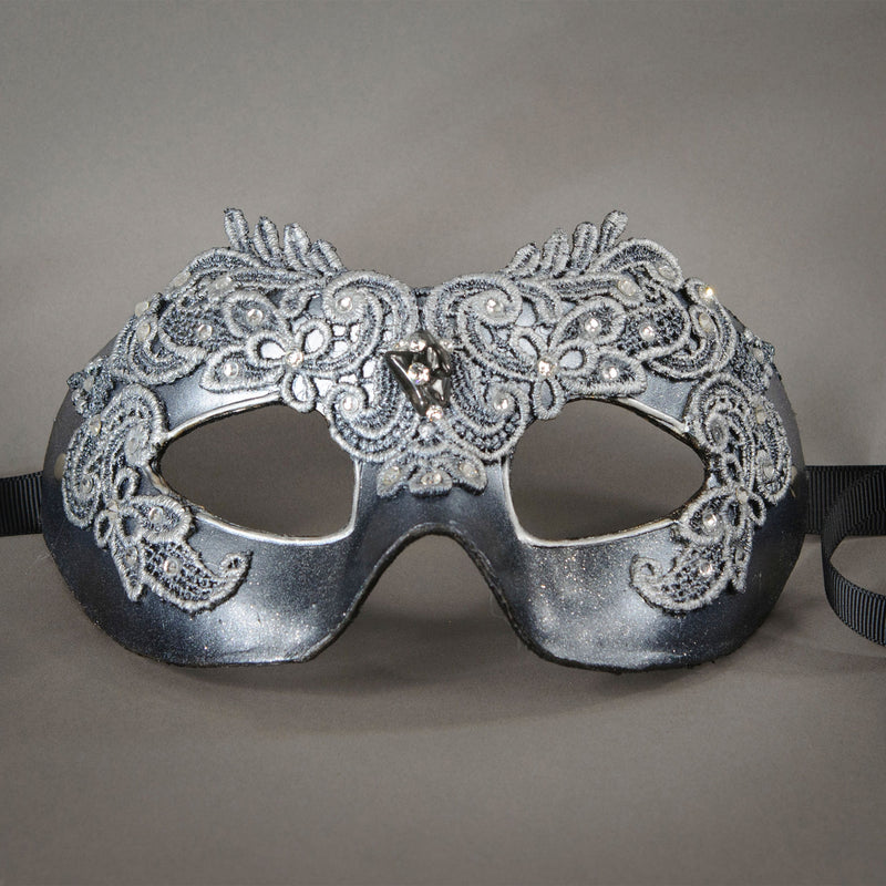 Simple, elegant eye mask in Metallic Silver and Black. Embellished with lacquered lace, glass gems, Swarovski crystals and polished stones.  Hand made in the USA using traditional Venetian paper-mache techniques. Lined in stretch velvet for comfort. Detail.