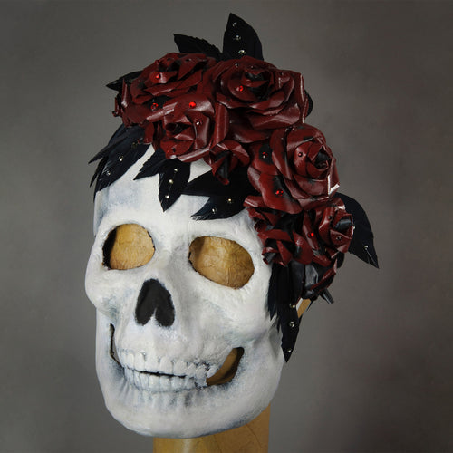 Perfect for Halloween or any dark themed masquerade, this skull mask is killer! The skull is framed with a bouquet of handmade lacquered paper roses with black feathered leaves, sprinkled with assorted Swarovski crystals.  Handmade in the USA using the traditional Venetian paper mache process. Lined with soft stretch velvet for comfort.
