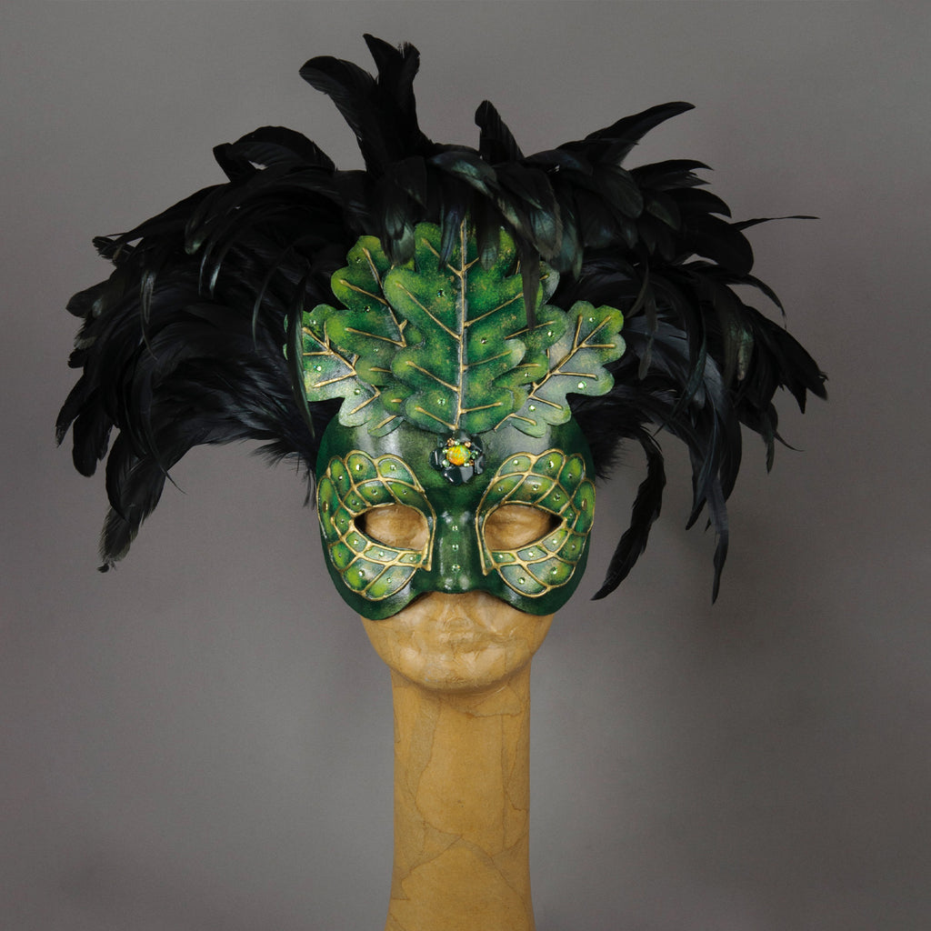 An apparition from the wooded forest, this beautiful Masquerade Mask, is one of our versions of the green man. With a backdrop crest of black coque feathers, the green handmade oak leaves stand proud. To add some sparkle, we embellished this mask with a complimentary palette of Swarovski crystals, dichroic glass and polished stones.  Hand made in the USA using traditional Venetian paper-mache technique. Lined with hypoallergenic stretch velvet for comfort.