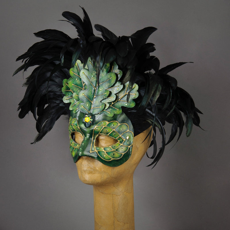 An apparition from the wooded forest, this beautiful Masquerade Mask, is one of our versions of the green man. With a backdrop crest of black coque feathers, the green handmade oak leaves stand proud. To add some sparkle, we embellished this mask with a complimentary palette of Swarovski crystals, dichroic glass and polished stones.  Hand made in the USA using traditional Venetian paper-mache technique. Lined with hypoallergenic stretch velvet for comfort. Side view.