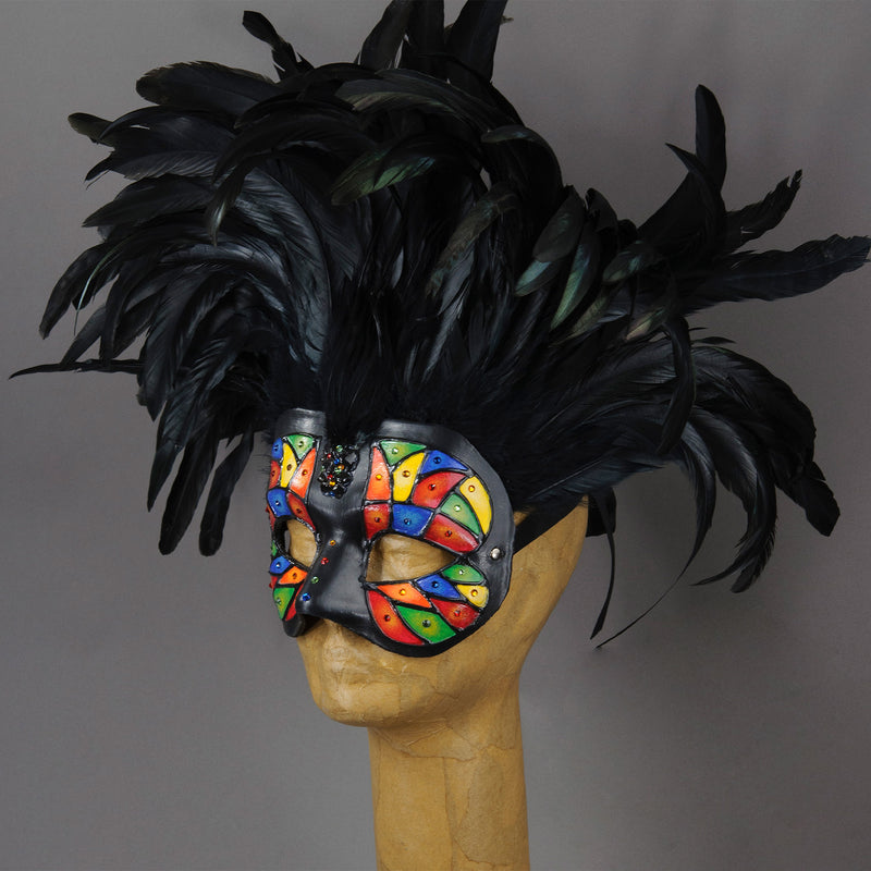 Beautiful Masquerade Mask, crested in Black coque feathers. Stained glass motif painted in rainbow colors and embellished with Swarovski crystals, dichroic glass and polished stones. Shades of red, orange, yellow, green and blue.  Hand made in the USA using traditional Venetian paper-mache technique. Lined with hypoallergenic stretch velvet for comfort. Side view.