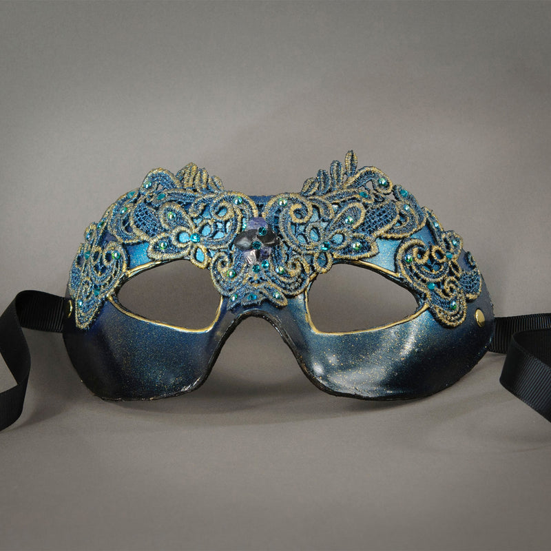 Simple, elegant eye mask in Metallic Turquoise Blue and Black. Embellished with lacquered lace, glass gems, Swarovski crystals and polished stones.  Hand made in the USA using traditional Venetian paper-mache techniques. Lined in stretch velvet for comfort. Detail.