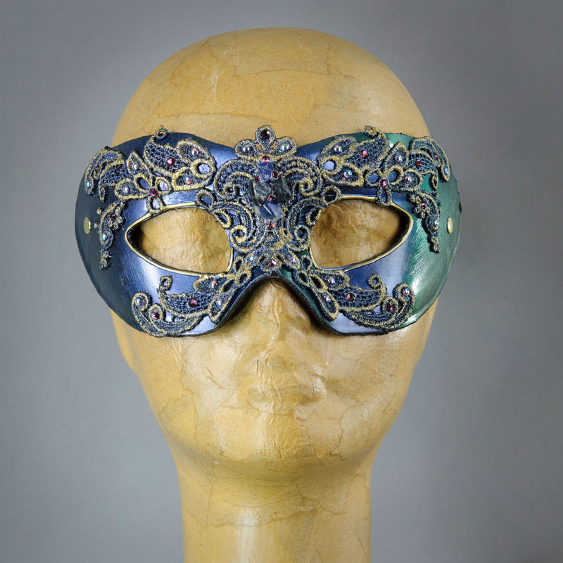 Simple, elegant eye mask in Iridescent Green, Blue and Black. Embellished with lacquered lace, glass gems, Swarovski crystals and polished stones.  Hand made in the USA using traditional Venetian paper-mache techniques. Lined in stretch velvet for comfort.