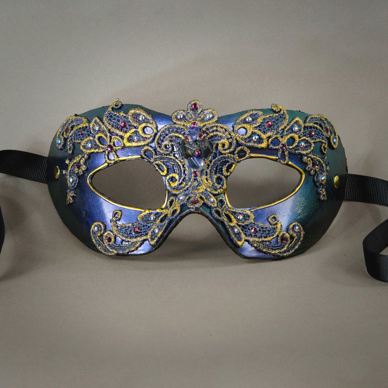 Simple, elegant eye mask in Iridescent Green, Blue and Black. Embellished with lacquered lace, glass gems, Swarovski crystals and polished stones.  Hand made in the USA using traditional Venetian paper-mache techniques. Lined in stretch velvet for comfort. Detail.