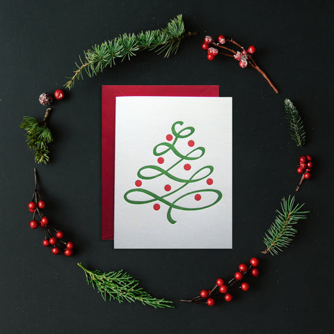 Letterpress holiday card styled with holly berries and spruce sprigs.
