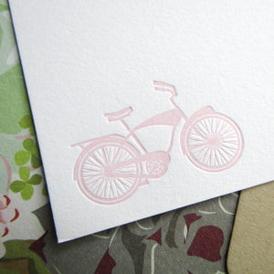 Letterpress pink bicycle image printed onto white cotton cards, shown with light brown envelopes lined with succulent papers, printed by inviting in Austin, Texas.