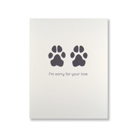 "Letterpress pet sympathy card of dog paw prints and ""I'm sorry for your loss"" printed in black ink."