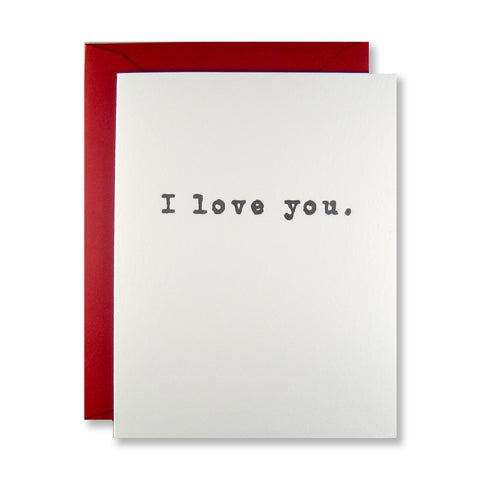 "Letterpress love card reads ""I love you."" in a simple typewriter font in black ink, with a red envelope."