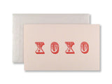 Letterpress Valentine's Day card, red XOXO on pink card with white glassine envelopes, designed & printed by inviting in Austin TX.