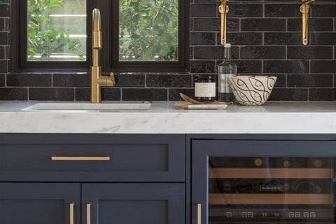 Dark blue cabinets with black subway tile via thespruce.com