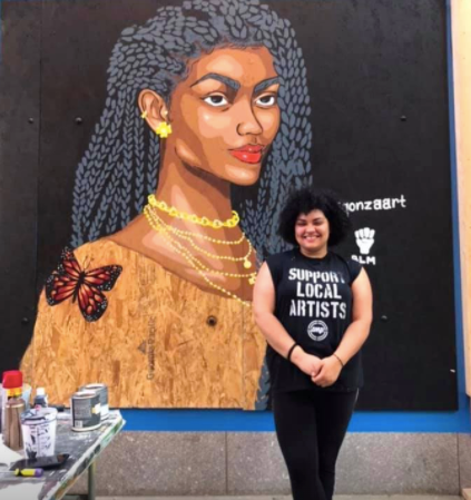 Artis Agonzo stands in front of her mural painted on a boarded up retail space