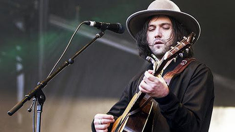 Conor Oberst performing live on stage with a guitar