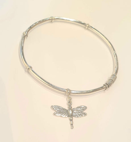 Round silver bangle with dragonfly hanging off it