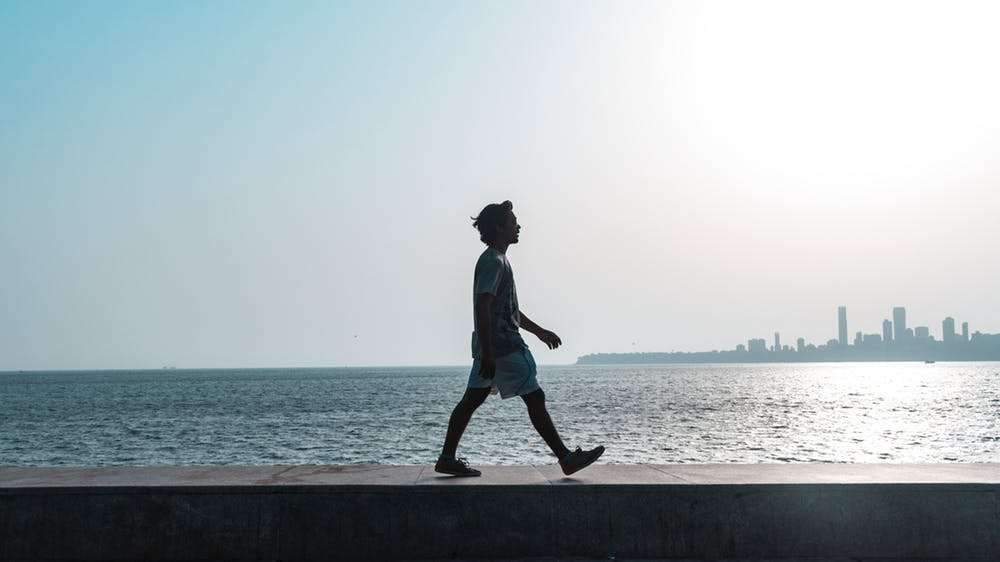 Person walking with water and city in background