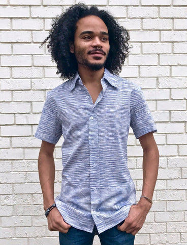 This Light Blue Ikat Men's Button Down Shirt from Passion Lilie features short sleeves, a light blue woven cotton, and a fitted silhouette, making it one of the Valentine's Day clothing gifts he'll love.