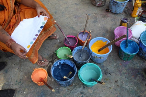 An Indian artisan mixes natural dyes in a variety of colors for Passion Lilie's clothing made in India.