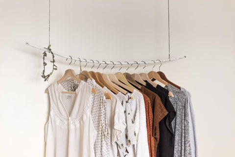 An artful display of blouses, sweaters, and other tops on hangers.