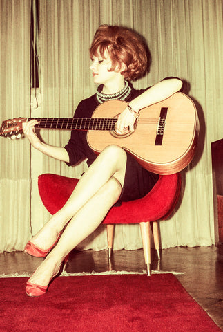 A woman from the 1960s strumming an acoustic guitar and wearing a minidress, whose hemline is above the knee and reflects the feminist political fashion trends of the time.
