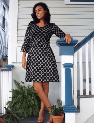 This Athena Organic Jersey Dress, which features long sleeves, a rich black color, and a unique white pattern, is the perfect go-to dress to get you through the fall season in style.