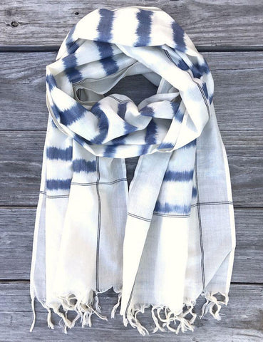 This Blue Striped Scarf from Passion Lilie features blue stripes on white handwoven fabric and tassels at the ends.