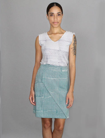 A model wearing our gray-and-white striped, sleeveless, Breton Striped Organic Jersey Top with our teal, white-spotted Halley Organic Jersey Skirt.