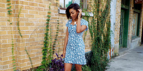 A woman wearing Passion Lilie's Green Garden Dress, a blue-green dress with white floral print, cap sleeves, and side pockets. Made in Bangalore through fair trade, this is a prime example of ethical, sustainable clothing.