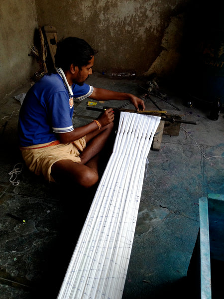 Hand loom weaver draws the design.