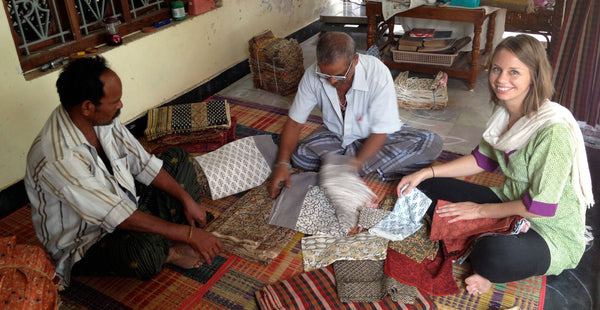 Fair trade artisans and the founder of Passion Lilie looking at fabric samples.
