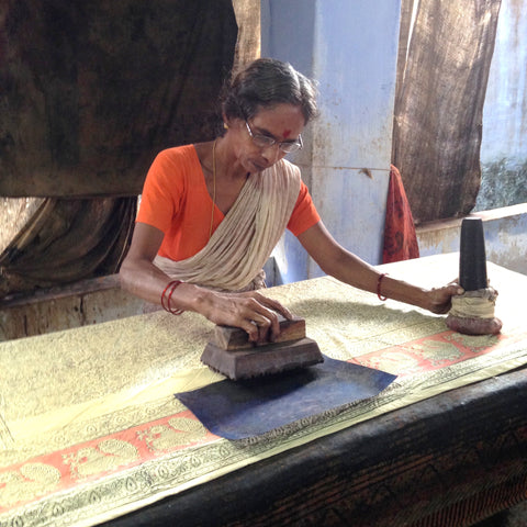 An Indian artisan hand block printing fabric for Passion Lilie, using a hammer to create the force needed to stamp the design onto the fabric.