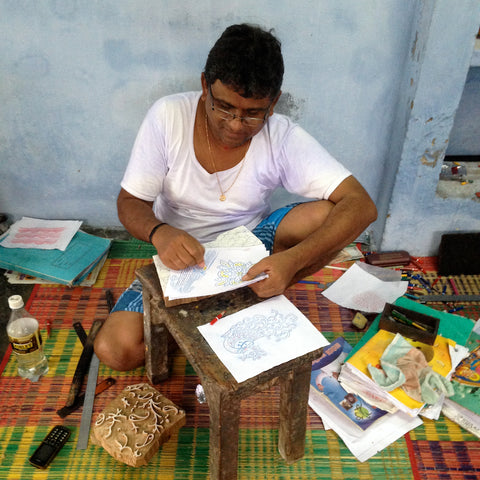 A craftsman tracing a design used for hand block printing in India.