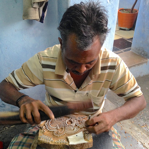 A craftsman chipping away at a wooden block, leaving it with a design that can be stamped onto fabric in the hand block printing process.