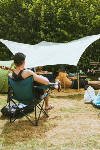 A group of young men relaxing under a shady canopy, playing guitar, taking photos, and using other items in our Festival Gear Guide.