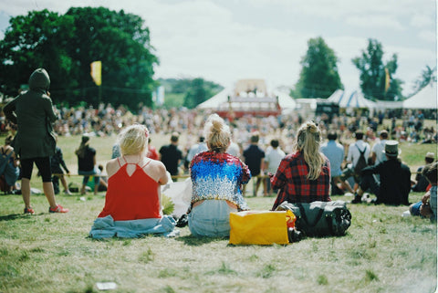 Three young women sitting on the music festival grounds and wearing stylish festival outfits.