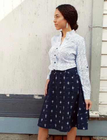 The Navy Stars Midi Skirt from Passion Lilie features a white star print on navy handwoven fabric, a wide waistband front, and pockets.