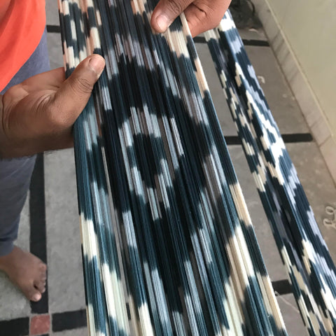 Ikat woven fabric from Passion Lilie, shown here in a white, blue, and turquoise diamond pattern and made with environmentally friendly dyes and materials.