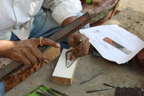 An artisan chipping away at a wood block as part of Passion Lilie's process for our clothes made in India.