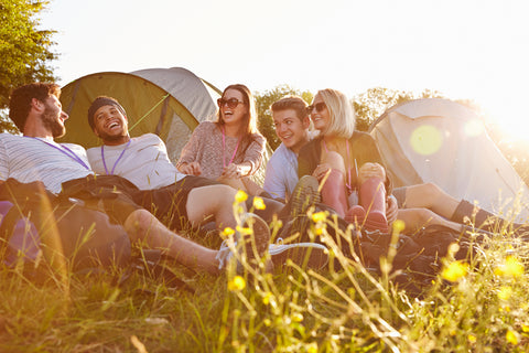 Young people hanging out by their tents, one of many items we recommend in our Festival Gear Guide.