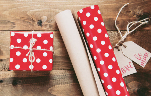 Red wrapping paper with white polka dots and a wrapped gift.